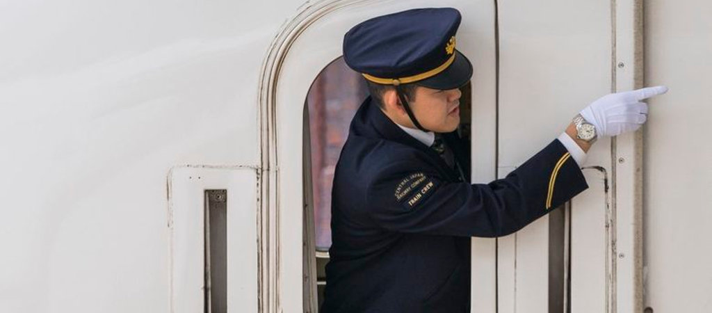 Guard on bullet train preparing to leave station, Kyoto, Japan